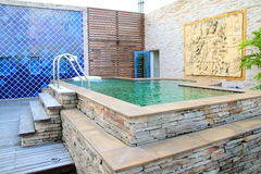 Outdoor jacuzzi with stone carving wall Stock Images