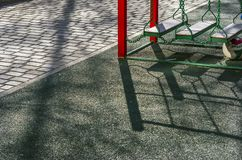 Outdoor Kids Playground Area, Paved Walkway in the Park on a Spring Afternoon with Long Shadows.  royalty free stock photo