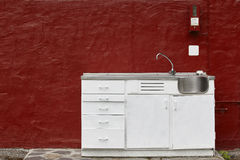 Outdoor kitchen cabinet sink and faucet over a red wall Stock Image