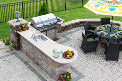 Outdoor kitchen and dining table on a paved patio. High angle view of a stylish outdoor kitchen, gas barbecue and dining table set for entertaining guests with Royalty Free Stock Photos