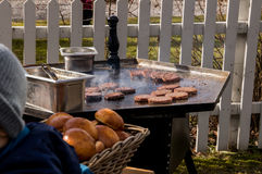 Outdoor kitchen hamburger sizzling on a frying table Stock Photo