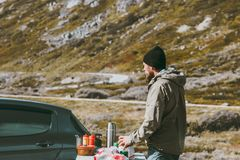 Outdoor kitchen Man cooking in mountains. During road trip by car wild nature Stock Images