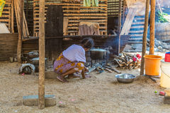 An outdoor kithchen with and old woman cooking food. Stock Images