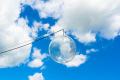 Outdoor lamp during daylight -. Transparent glass ball with bulb is on the string. Blue sky with white clouds in the background. Copy space around light royalty free stock images
