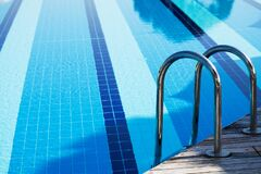 Free Outdoor Large Blue Swimming Pool On Site With Stairs To Descend Into The Water. Sunbeds And Sun Umbrellas Stock Image - 169860671