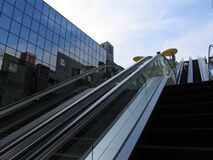 Outdoor large escalator staircase close to a skyscraper
