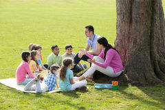 Outdoor Lesson. Small group of children sitting on the grass having a lesson outdoors. Male and female teacher can be seen. The children look to be listening and royalty free stock images