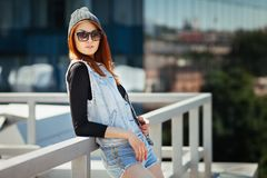 Outdoor lifestyle fashion portrait of pretty young girl, wearing in hipster swag grunge style urban background. Red hair stock photos