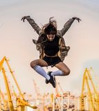 Outdoor lifestyle image of a young pretty chestnut haired caucasian girl having fun, jumping and dancing. Cute casual royalty free stock images
