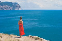 Woman in red dress looking at sea. Outdoor lifestyle photo of woman in red dress looking at sea. Travel background. Tourism Royalty Free Stock Photo