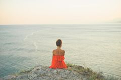 Woman in red dress looking at sea. Outdoor lifestyle photo of woman in red dress looking at sea. Travel background. Tourism Royalty Free Stock Images