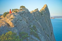 Woman in red dress walking on rock. Outdoor lifestyle photo of woman in red dress walking on rock. Travel background. Tourism Royalty Free Stock Images