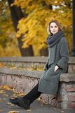 Outdoor lifestyle photo of young beautiful blonde woman in fall autumn park cozy scarf grey vintage coat. Film filter effects. Outdoor lifestyle photo of young stock photos
