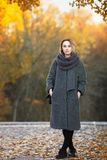 Outdoor lifestyle photo of young beautiful blonde woman in fall autumn park cozy scarf grey vintage coat. Film filter effects. Outdoor lifestyle photo of young stock photography