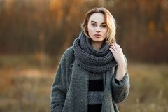 Outdoor lifestyle photo of young beautiful blonde woman in fall autumn park cozy scarf grey vintage coat. Film filter effects. Outdoor lifestyle photo of young royalty free stock photos
