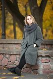 Outdoor lifestyle photo of young beautiful blonde woman in fall autumn park cozy scarf grey vintage coat. Film filter effects. Outdoor lifestyle photo of young stock image