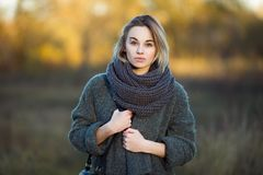 Outdoor lifestyle photo of young beautiful blonde woman in fall autumn park cozy scarf grey vintage coat. Film filter effects. Outdoor lifestyle photo of young stock photo