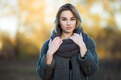 Outdoor lifestyle photo of young beautiful blonde woman in fall autumn park cozy scarf grey vintage coat. Film filter effects. Outdoor lifestyle photo of young royalty free stock images