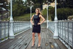 Outdoor lifestyle portrait of blonde young woman in stylish black dress staying on bridge on the street. Autumn, rainy day Stock Images