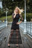 Outdoor lifestyle portrait of blonde young woman in stylish black dress staying on bridge on the street. Autumn, rainy day Stock Photos