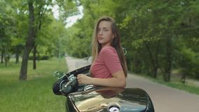 Portrait of charming girl sitting on motorcycle. Outdoor lifestyle portrait of charming biker girl with long blond straight hair sitting on custom motorcycle stock footage
