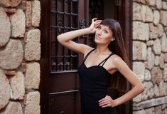 Outdoor lifestyle portrait of pretty young girl posing near old vintage wall and door, wearing in black dress on urban background. Creative gel polish royalty free stock photo