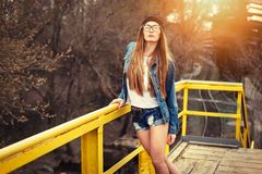 Outdoor lifestyle portrait of pretty young girl, wearing bright hipster swag dress, urban background royalty free stock images