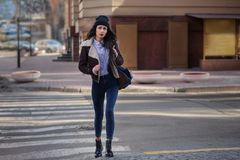Outdoor lifestyle portrait of pretty young girl, wearing in hipster swag grunge style on urban background. Wearing hat and jeans. With backpack. Spring fashion royalty free stock images