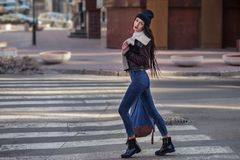 Outdoor lifestyle portrait of pretty young girl, wearing hipster swag grunge style on urban background. Wearing hat and jeans with. Backpack. Spring fashion stock photo