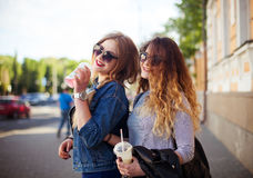Outdoor lifestyle portrait of two happy best friend girls walk laugh talk and drink lemonade. Girls laugh at the joke. Outdoor lifestyle portrait of two happy Royalty Free Stock Images
