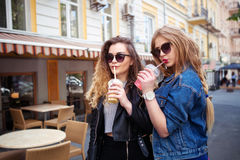 Outdoor lifestyle portrait of two happy best friend girls walk laugh talk and drink lemonade. Wearing trendy bright clothes and sunglasses Stock Photography