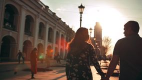 Outdoor lifestyle portrait of young couple in love walking in city on the street behind sunset
