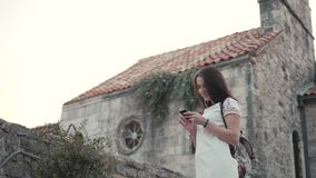 Outdoor Lifestyle Portrait of Young Woman Using Smartphone, Travel With Backpack, Stylish Casual Outfit, Evening Sunset stock footage