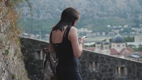 Outdoor Lifestyle Portrait of Young Woman Using Smartphone, Travel With Backpack, Stylish Casual Outfit, Evening Sunset. 4K stock video footage