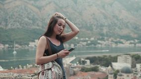 Outdoor Lifestyle Portrait of Young Woman Using Smartphone, Travel With Backpack, Stylish Casual Outfit, Evening Sunset stock video