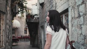 Outdoor Lifestyle Portrait of Young Woman Walking Down The Street At Old Town, Travel With Backpack, Stylish Casual. Outfit, Evening Sunset, 4K stock video