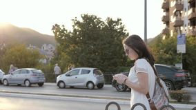 Outdoor Lifestyle Portrait of Young Woman Walking Down The Street Using Smartphone, Travel With Backpack, Stylish Casual stock footage