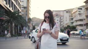 Outdoor Lifestyle Portrait of Young Woman Walking Down The Street Using Smartphone, Travel With Backpack, Stylish Casual. Outfit, Evening Sunset, 4K stock footage