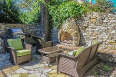 Outdoor living - rock wall and built-in outdoor fireplace built around a corner tree with wicker furniture and an electric outdoor stock image