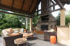 Outdoor Living Room. An upscale backyard terrace featuring perennials and with a custom designed shelter and fireplace Royalty Free Stock Photo