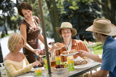 Outdoor lunch with friends. Happy young friends sharing a picnic in the summer Royalty Free Stock Photo