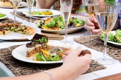 Outdoor lunch party table setting with food. Hand and party food on beautifully set table, healthy salad and tart for lunch garden party Royalty Free Stock Photos