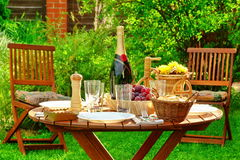 Outdoor Lunch Table With Bottle Of Wine On The Backyard Stock Photo