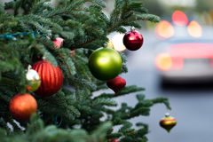 Outdoor Mall Christmas Tree. Close up of Christmas tree with cars in background Royalty Free Stock Photography