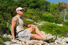 Outdoor man resting on rock after hiking Royalty Free Stock Photo