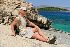 Outdoor man resting on rock after hiking Royalty Free Stock Photos
