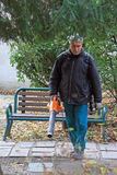 Outdoor manual worker is cleaning the fallen leaves. Venice, Italy - November 23, 2015: outdoor manual worker is cleaning the fallen leaves in park by blower in Stock Photography