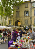 Outdoor Market, Aix-en-Provence, France. A  man and woman discuss a potential sale in a weekend outdoor market of collectibles in a small square surrounded by Royalty Free Stock Images