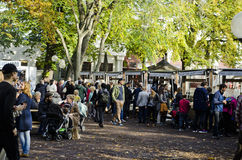 Outdoor market with lots of people in groups. Market day outdoors with a big group of people standing, sitting, looking and talking, food vendors and sellers. A stock images