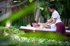 Outdoor Massage. A young woman gets a massage outside in a tropical environment Royalty Free Stock Photos